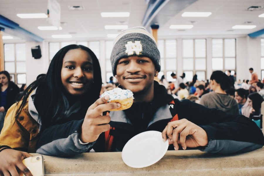 Juniors+Kyah+Walker+and+Jaylen+Wright+enjoy+a+donut+at+the+honor+roll+breakfast.