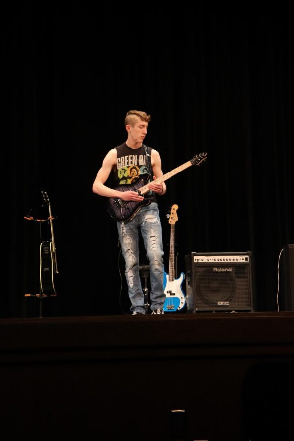Ryan Downey finishes his performance with Riley Morgan's guitar.